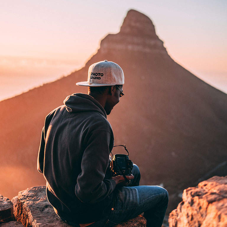 Young man with sunglasses, cap and hoodie exercising and taking photo's with his camera in a mountainous area in the early morning.