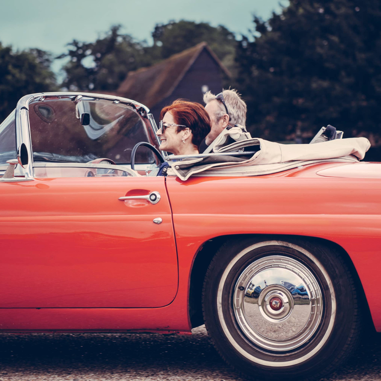 An elderly couple taking a leisurely drive in their classic red cabriolet car with the roof top down.