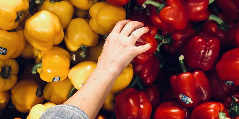 Red and yellow fresh bell peppers with a woman's hand choosing a red bell pepper at the market.
