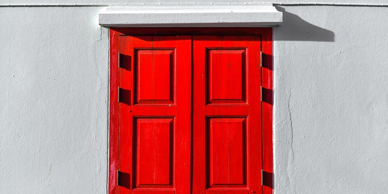 A gray building with a red wooden door.