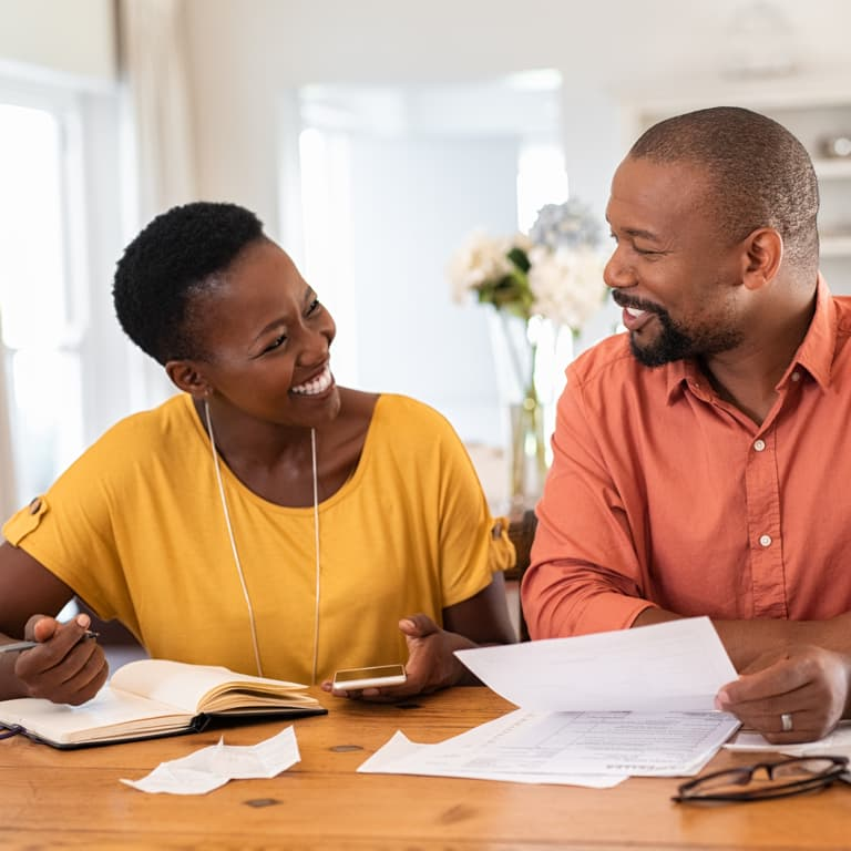 A husband and wife look at each other smiling while reviewing their tax and retirement and investment goals.