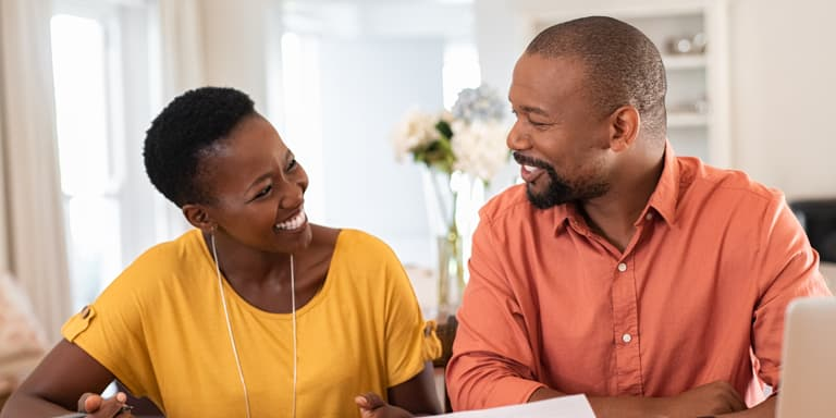 Alt tag: A husband and wife look at each other smiling while reviewing their tax and retirement and investment goals.
